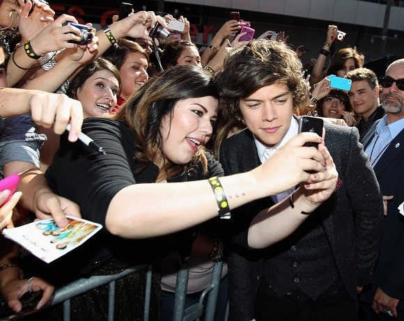 Fan taking selfie with One Direction's Harry Styles
